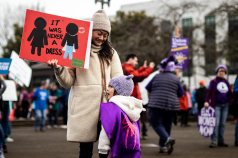 """It was Never a dress,"" sign held up by a mother. Her daughter wears a cape."