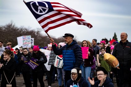 """Protestor waves American """"Peace"""" flag during one of the speeches."""