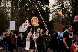 Marchers holds up Trump Piñata while they march.